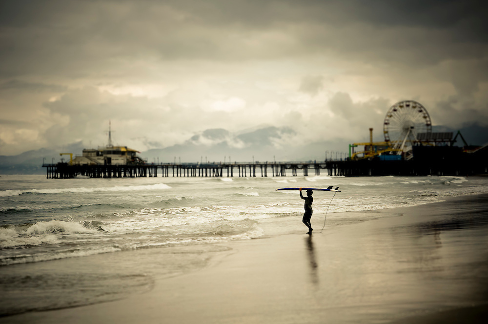 A surfer heads to the water by the Santa Monica Pier, Santa Monica Beach, California.