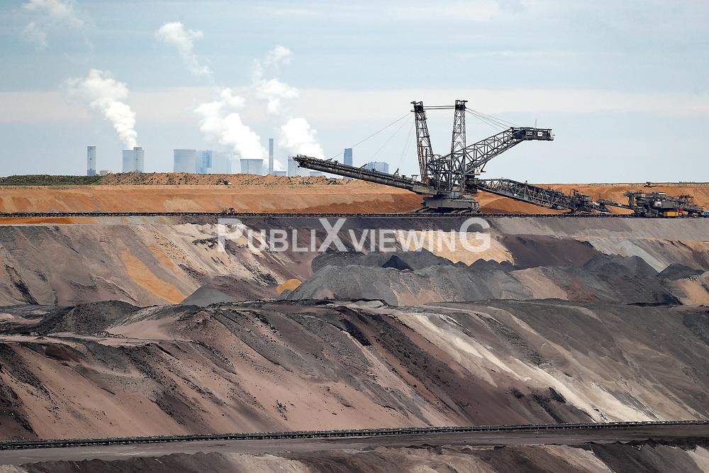 Ein Bagger f&ouml;rdert Braunkohle zur Energiegewinnung im Tagebau Garzweiler in Nordrhein-Westfalen. Im Hinergrund ein Kohlekraftwerk.<br /> <br /> Ort: Garzweiler<br /> Copyright: Andreas Conradt<br /> Quelle: PubliXviewinG