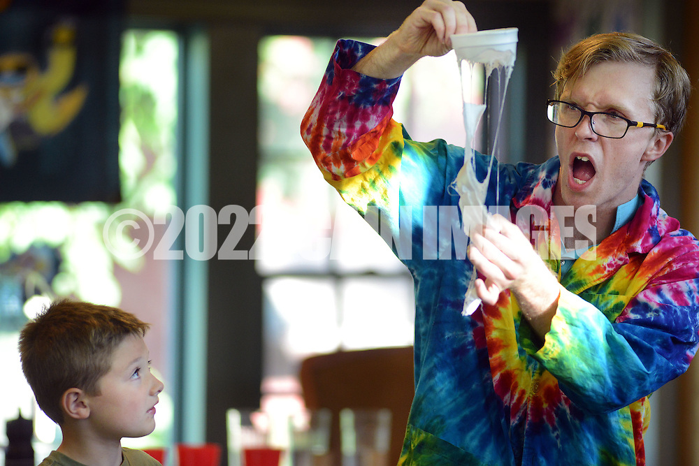 Scienceteller Taylor Darden (right) pulls apart a styrofoam cup after Brody Sweigard (left) poured acetone over it during the Sciencetellers show Thursday July 23, 2015 at the Union Library in Hatboro, Pennsylvania. Sciencetellers teach science to their audience by telling a lively, interactive and exciting story intertwined with basic science principles. (Photo by William Thomas Cain)