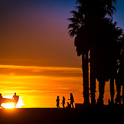 Surfers and beachgoers alike are silhouetted by a setting sun at surfer's point in Ventura, CA