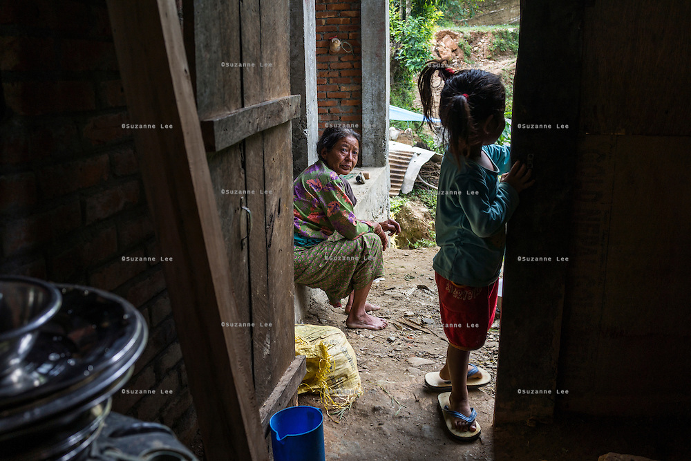 Bhagawati Baniya (56) watches as her grand daughter Aastha Baniya (6, in blue) plays near the kithen in their temporary home in Chautara, Sindhupalchowk, Nepal on 29 June 2015. The three girls lost their mother during the April 25th earthquake that completely levelled their house. Aastha was buried under the rubble together with her mother but Aastha survived. As their father Ratna Baniya (28) cannot care for the children on his own, SOS Childrens Villages has since been supporting the grandmother with financial and social support so that she can manage to raise the children comfortably and ensure that they will all be schooled. Photo by Suzanne Lee for SOS Children's Villages