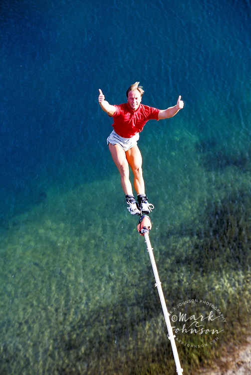 Australia, Gold Coast, bungy jumper over pond giving thumbs up