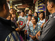 10 SEPTEMBER 2015 - BANGKOK, THAILAND: Residents watch as demolition crews wreck Chaiyasit Kittiwanitchapant's home. Authorities started to destroy 54 homes in front of Wat Kalayanamit, a historic Buddhist temple on the Chao Phraya River in the Thonburi section of Bangkok. Government officials, protected by police, seized the house of Chaiyasit Kittiwanitchapant, a Kanlayanamit community leader, who has led protests against the temple's abbot for trying to evict community members whose houses are located around the temple. Work crews went into Chaiyasit's home and took it apart piece by piece. The abbot of the temple said he was evicting the residents, who have lived on the temple grounds for generations, because their homes are unsafe and because he wants to improve the temple grounds. The evictions are a part of a Bangkok trend, especially along the Chao Phraya River and BTS light rail lines, of low income people being evicted from their long time homes to make way for urban renewal.     PHOTO BY JACK KURTZ