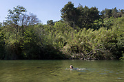 A woman swims in shallow and warm, natural waters of the River Orbieu, on 25th May, 2017, in Ribaute, Languedoc-Rousillon, south of France