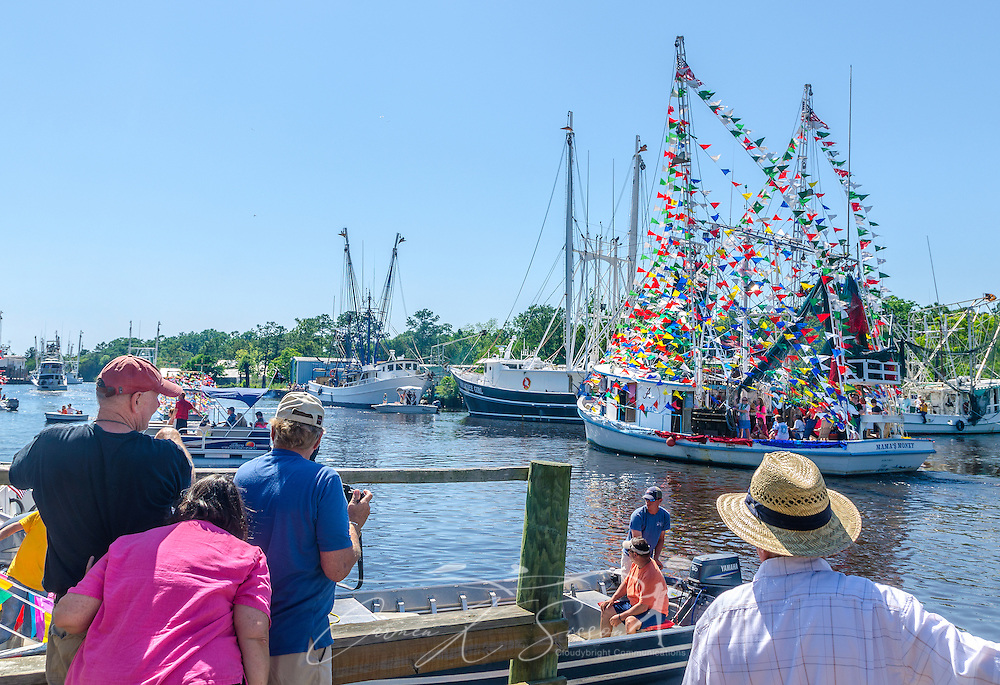 Spectators watch as decorated boats parade through the bayou during the 65th annual Blessing of the Fleet in Bayou La Batre, Alabama, May 4, 2014. The first fleet blessing was held by St. Margaret's Catholic Church in 1949, carrying on a long European tradition of asking God's favor for a bountiful seafood harvest and protection from the perils of the sea. The highlight of the event is a blessing of the boats by the local Catholic archbishop and the tossing of a ceremonial wreath in memory of those who have lost their lives at sea. The event also includes a land parade and a parade of decorated boats that slowly cruise through the bayou. (Photo by Carmen K. Sisson/Cloudybright)