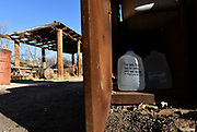 """Containers of water have been placed at an abandoned structure along a known smuggling route on the Buenos Aires National Wildlife Refuge as an act of humanitarian aid north of the U.S./Mexico border near Arivaca, Arizona, USA. Welcoming messages, the date, and the words """"Mills College"""" are written on the jugs."""