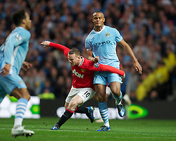 MANCHESTER, ENGLAND - Monday, April 30, 2012: Manchester City's Vincent Kompany in action against Manchester United's Wayne Rooney during the Premiership match at the City of Manchester Stadium. (Pic by David Rawcliffe/Propaganda)