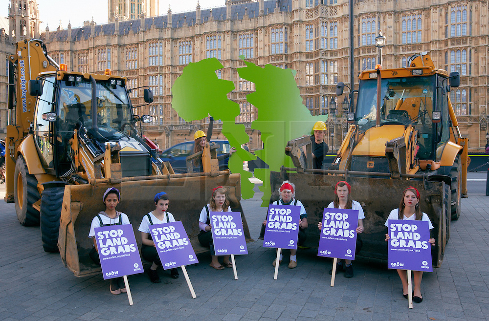 © Licensed to London News Pictures.  04/10/2012. LONDON, UK. Oxfam employees dressed as land girls sit on a JCB outside the Houses of Parliament to highlight the problem of land grabs. The charity calculates that an area of the size of London is sold to foreign investors every six days in the poorest countries on earth driving up food prices. Photo credit :  Cliff Hide/LNP