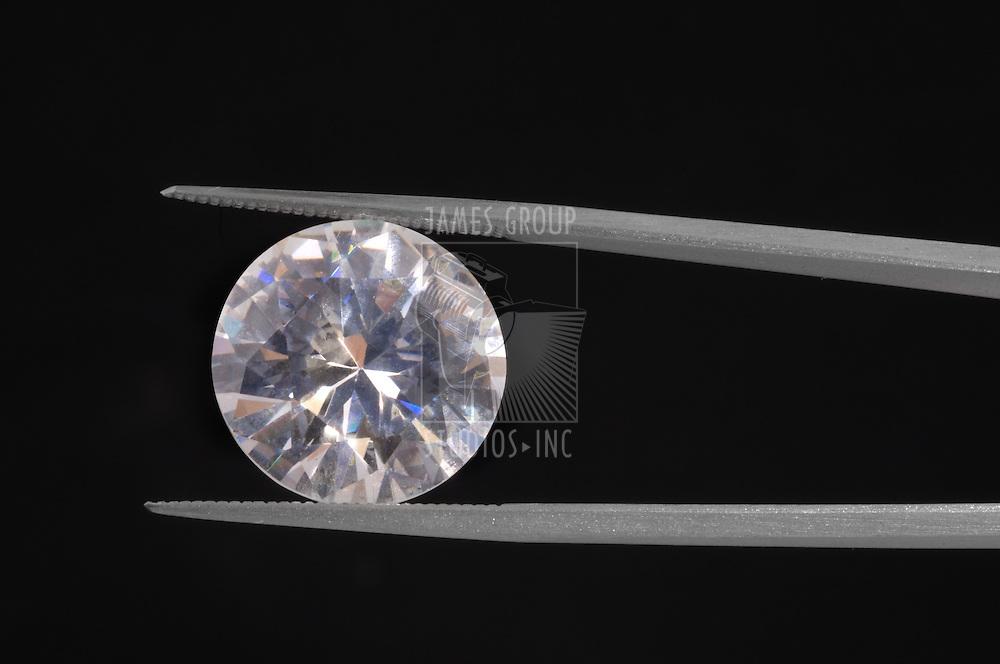 Diamond held by a gem tweezer shot on black