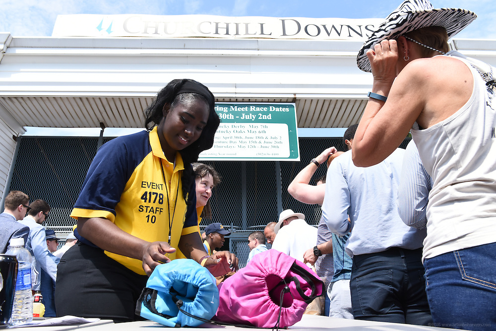 Bianca Russell, left, and Holly Nagorney, both of Cleveland, Ohio, check bags for prohibited items at Gate 3, the entrance to the infield for the 142nd running of the Kentucky Derby. May 7, 2016