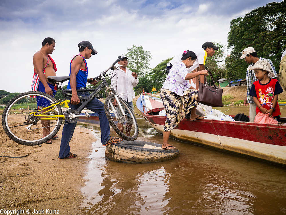 23 MAY 2013 - MAE SOT, TAK, THAILAND:  People board a boat at an unofficial border crossing point on the Moei River in Mae Sot, Thailand, to go back to Myawaddy, Myanmar. Fifty years of political turmoil in Burma (Myanmar) has led millions of Burmese to leave their country. Many have settled in neighboring Thailand. Mae Sot, on the Mae Nam Moei (Moei River) is the center of the Burmese emigre community in central western Thailand. There are hundreds of thousands of Burmese refugees and migrants in the area. Many live a shadowy existence without papers and without recourse if they cross Thai authorities. The Burmese have their own schools and hospitals (with funding provided by NGOs). Burmese restaurants and tea houses are common in the area.     PHOTO BY JACK KURTZ