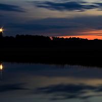 The Assateague Light House (rebuilt 1866) with the twilight sky reflected in the Assateague Channel, Chincoteague National Wildlife Refuge, Assateague Island, Virginia.