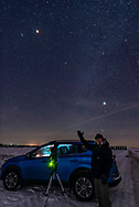 A selfie of the successful eclipse chaser bagging his trophy, the total lunar eclipse of January 20, 2019. This was from a site south of Lloydminster on the Alberta-Saskatchewan border, but just over into the Saskatchewan side. The area promised the best prospects for clear skies this night and predictions proved accurate, and made the 5-hour drive north from home well worth it.<br /> <br /> This is an untracked single exposure of 15 seconds at ISO 3200 and f/2.8 with the Sigma 20mm Art lens and Nikon D750. However, I blended in a shorter 1-second exposure for the red eclipsed Moon itself to prevent its disk from overexposing as it would in any exposure long enough to record the Milky Way. The eye can see both eclipsed Moon and Milky Way together in the sky at once, but the camera cannot. So it takes a blend of exposures to show the sky the way the eye saw it. <br /> <br /> In the picture is my other camera in use that night, the Canon 6D MkII with a 200mm lens on a Fornax tracker for taking tracked close-ups of the Moon near the Beehive star cluster. The green light is from the dew heater in use around the lens to ward off frost over the 4 hour shoot.