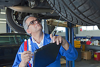 Mechanic analyzing car engine at auto repair shop