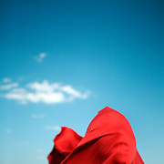 A woman wrapped in a red cloth stands on a beach, the wind pressing the cloth into her shape