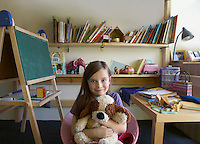 Girl (5-6) sitting in room hugging soft toy