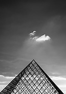 I.M.Pei's iconic Pyramid at the Louvre museum, Paris, is silhouetted against an evening sky with a small cloud above.