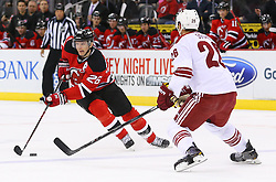 Mar 27, 2014; Newark, NJ, USA; New Jersey Devils left wing Patrik Elias (26) skates with the puck while being defended by Phoenix Coyotes defenseman Michael Stone (26) during the first period at Prudential Center.