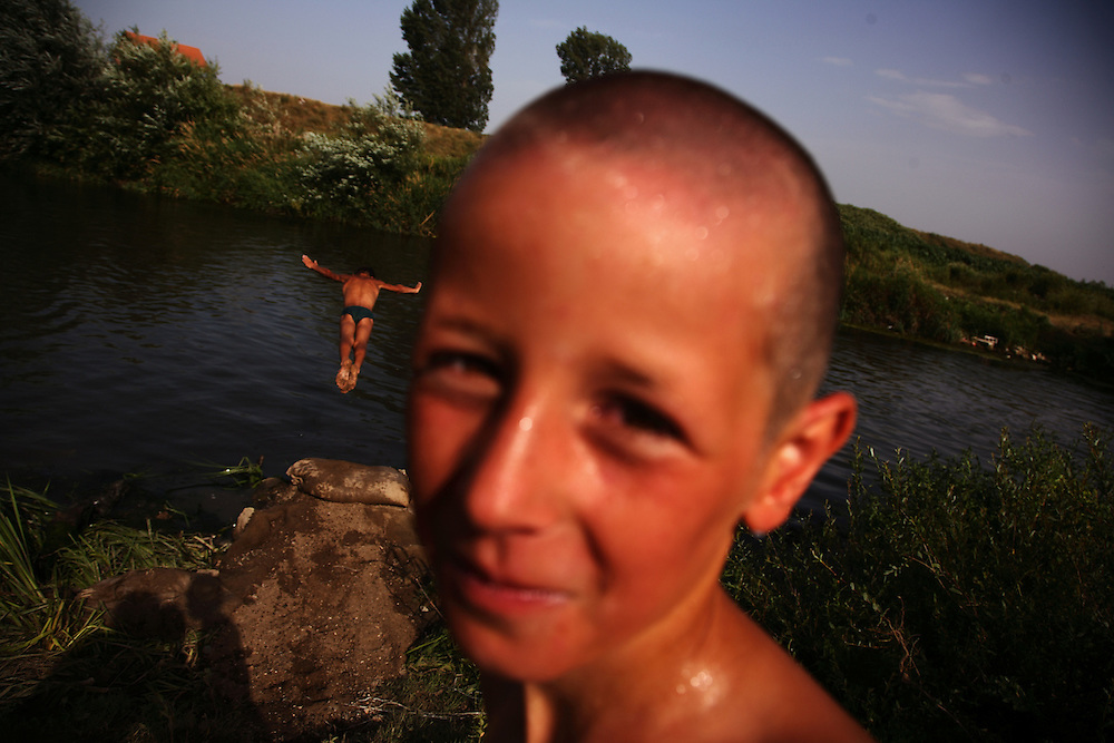 Children playing in a polluted river near a community garbage dump on the outskirts of Vushtrri, Kosovo..