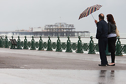 © under license to London News Pictures. 12/06/12. Heavy rainfall across the south east, two people walk along brighton seafront in the rain. The met office has issued severe weather warnings in England and Wales. Unseasonal weather in the south east has caused flooding across Sussex has been badly hit. Brighton XAVIER ITTER/LNP