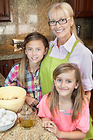Portrait of a senior woman with granddaughters in kitchen