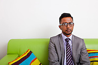 Businessman sitting on sofa looking at camera