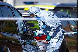 A forensics investigator dusts a private hire MPV for prints at the scene at the intersection of Cole Crescent and Scott Crescent in Harrow where a 17-year-old was stabbed on the night of Sunday 10th June, leaving him in critical condition. June 11 2018.
