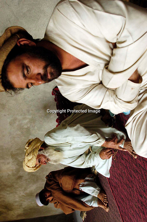 Asaldin(c) and his sons Nabi Khan and Shahpoor(r) talk about his other son Dilawar at their home in the the town of Yakubi in the district of Khost, Afghanistan May 2, 2005.  Diliwar, a 22-year-old farmer and part-time taxi driver, died in December 2002 while being held in the main United States air base at Bagram, north of Kabul. His death was ruled a homicide by the Army medical examiner.<br /> <br /> <br /> Photo by Keith Bedford