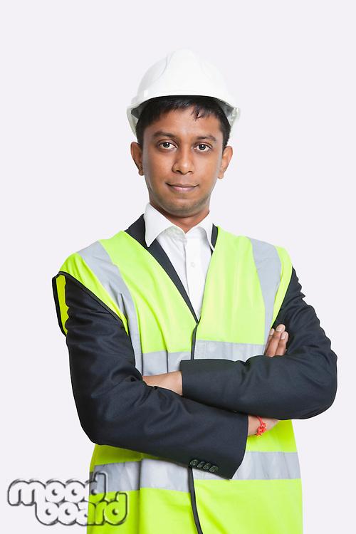 Portrait of confident Asian architect wearing reflective vest against white background