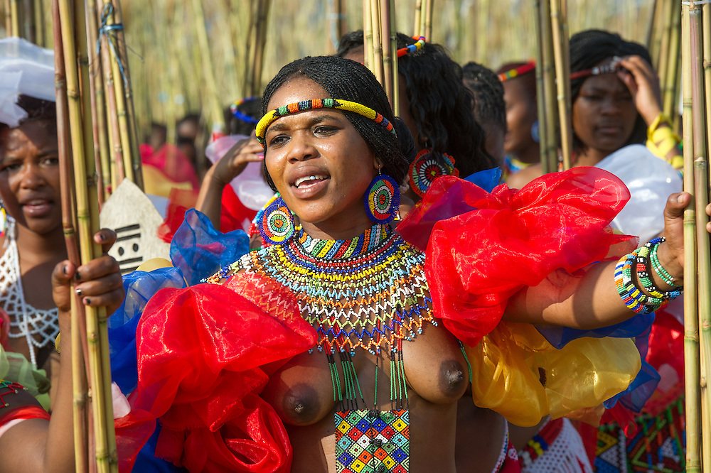 Ludzidzini, Swaziland, Africa - The Swazi Umhlanga, or reed dance ceremony, 100,000 unmarried women , or maidens, celebrate their virginity by bringing reeds for the Swazi Queen Mother's Kraal during this 8 day long annual tradition and dancing in a massive gathering before King Mswati III, the royal family, and the public.