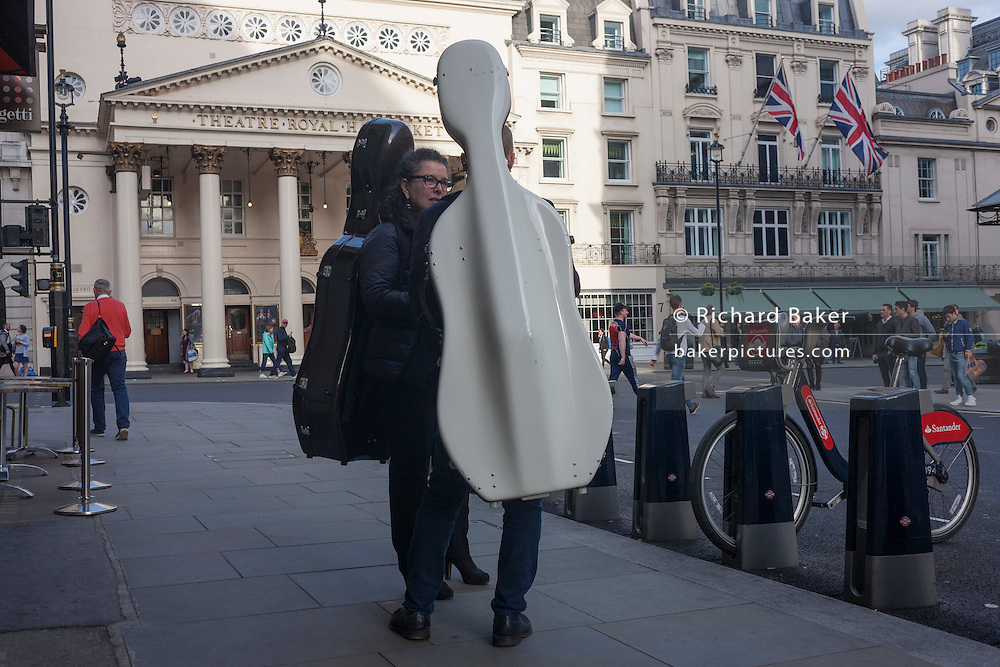 Two cellists chat in the street, opposite the Theatre Royal Harmaket, in central London.