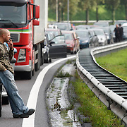 Nederland Rotterdam 30-09-2010 20100930..File op de rijksweg A16 op de oosterlijke ring, lange rijen met auto's staan stil. Man is uit auto gestapt om en rookt een sigaret. mensen, roken.  Traffic jam. Holland, The Netherlands, dutch, Pays Bas, Europe ..Foto: David Rozing