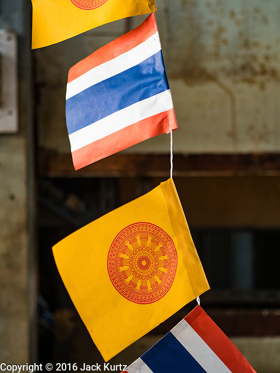 05 JANUARY 2016 - BANGKOK, THAILAND:          Thai (red, white and blue stripes) and Buddhist (solid yellow with dharma wheel) flags hang in an empty stall in the closed Bang Chak Market. The market closed permanently on January 4, 2016. The Bang Chak Market served the community around Sois 91-97 on Sukhumvit Road in the Bangkok suburbs. Bangkok city authorities put up notices in late November that the market would be closed by January 1, 2016 and redevelopment would start shortly after that. Market vendors said condominiums are being built on the land.                   PHOTO BY JACK KURTZ