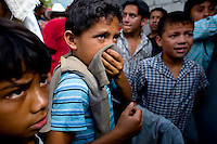 A young boy covers his mouth from tear gas as residents take to the streets after a clash with local police Monday Sept. 10 2007, Palin Guatemala. Residents accuse the mayor of, among other things, of bussing voters for the elections on Sept. 9 2007.   (photo by/ Darren Hauck)..