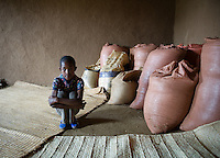 Farmer's child from the Sodo region of Ethiopia keeping a watchful eye over their grain which occupies the corner of their home before sale or planting . Photo:Andrew Downes