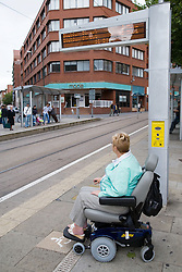 Woman wheelchair user waiting at a tram stop,