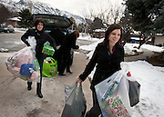 LDS Hospital employee Anna Heaps, right, brings in bagfuls of gifts to the Sebaske residence in Sandy, Monday, Dec. 17, 2012.