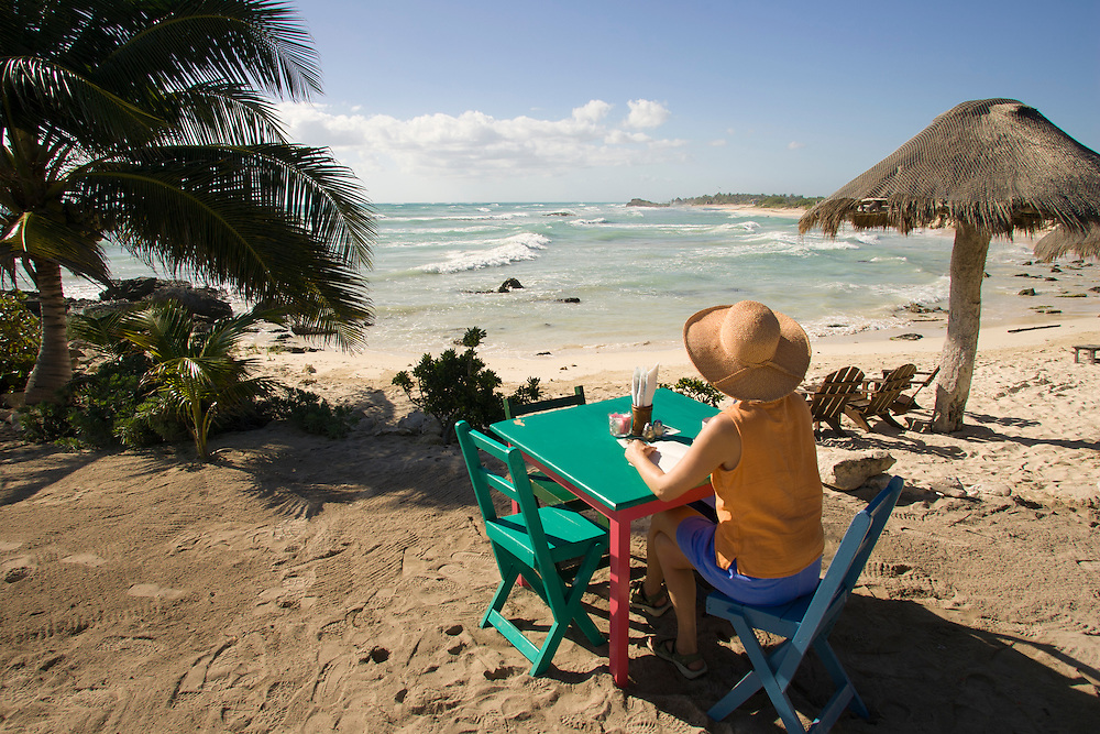 Mexico, Yucatan, Tulum, female tourist at restaurant on beach by Caribbean Sea.  MR