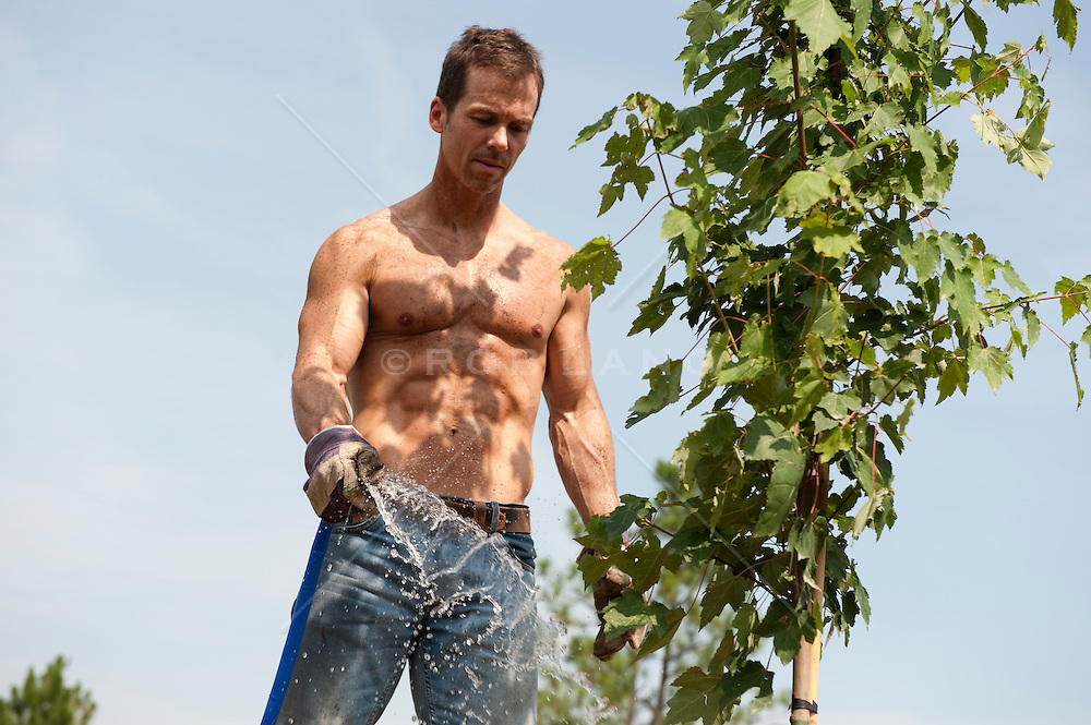 Man without a shirt watering a tree