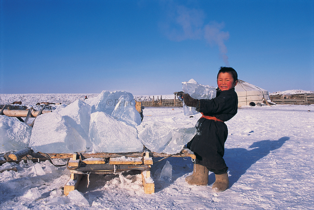 Darkhad boy fetching ice to melt for water<br /> Winter water storage<br /> Darkhadyn Khotgor Depression<br /> Mongolia