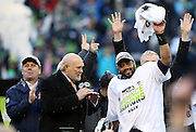 (L-R) Former Seattle Seahawks wide receiver Steve Largent looks on as football analyst and former Pittsburgh Steelers quarterback Terry Bradshaw watches Seattle Seahawks quarterback Russell Wilson (3) wave his towel and celebrate after the Seattle Seahawks win the NFL week 20 NFC Championship football game against the Green Bay Packers on Sunday, Jan. 18, 2015 in Seattle. The Seahawks won the game 28-22 in overtime. ©Paul Anthony Spinelli