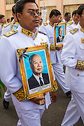 "01 FEBRUARY 2013 - PHNOM PENH, CAMBODIA:  Mourners carry photos of former Cambodian King Norodom Sihanouk as they follow his funeral procession through Phnom Penh. Norodom Sihanouk (31 October 1922 - 15 October 2012) was the King of Cambodia from 1941 to 1955 and again from 1993 to 2004. He was the effective ruler of Cambodia from 1953 to 1970. After his second abdication in 2004, he was given the honorific of ""The King-Father of Cambodia."" Sihanouk died in Beijing, China, where he was receiving medical care, on Oct. 15, 2012. His cremation is will be on Feb. 4, 2013. Over a million people are expected to attend the service.   PHOTO BY JACK KURTZ"