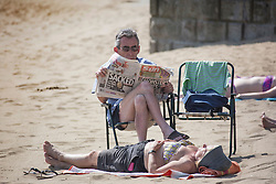 © Licensed to London News Pictures. 01/07/2015. Scarborough, UK. A couple sunbath on Scarborough beach. Britain is set to sizzle in temperatures of up to 34C (93F) today, with forecasters predicting the hottest day for several years. A tropical air mass moving from North Africa, Spain and Portugal means that we could be hotter than Rio de Janeiro. Photo credit : Andrew McCaren/LNP
