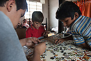 Ariel Barrios (left) solves a puzzle with Facundo, 9 (center), and Alberto, 9. In the background is community leader Lorena Pastoriza.