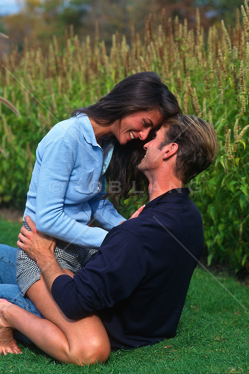 couple being playful and romantic on a grassy lawn