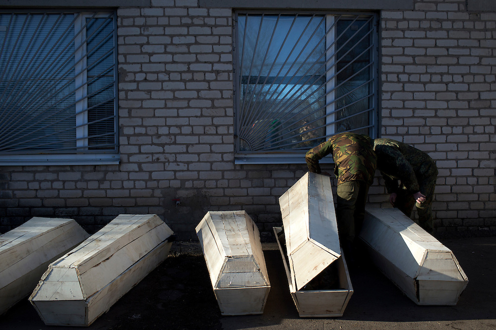 Soldiers at the morgue check coffins containing their comrades on February 18, 2015 in Artemivsk, Ukraine.