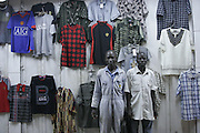Men selling shirts at their market stall. Kampala at night. Uganda. Africa.