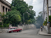 Woman looks for a ride share taxi, as a classic station wagon automobile takes the corner and the thick black exhaust settles from a city bus in Vedado, Havana.