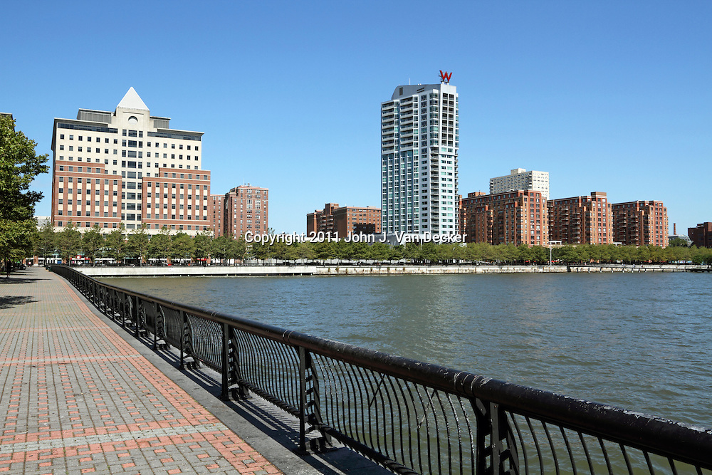 The Hoboken, New Jersey waterfront as viewed from the park on Pier A. The white W Hotel is visible with condominium buildings to the left and right.  Hoboken was once a transportation and warehouse hub but has been gentrified over the last 30 years to be an upscale community across the Hudson River from New York City. Hoboken, NJ, USA