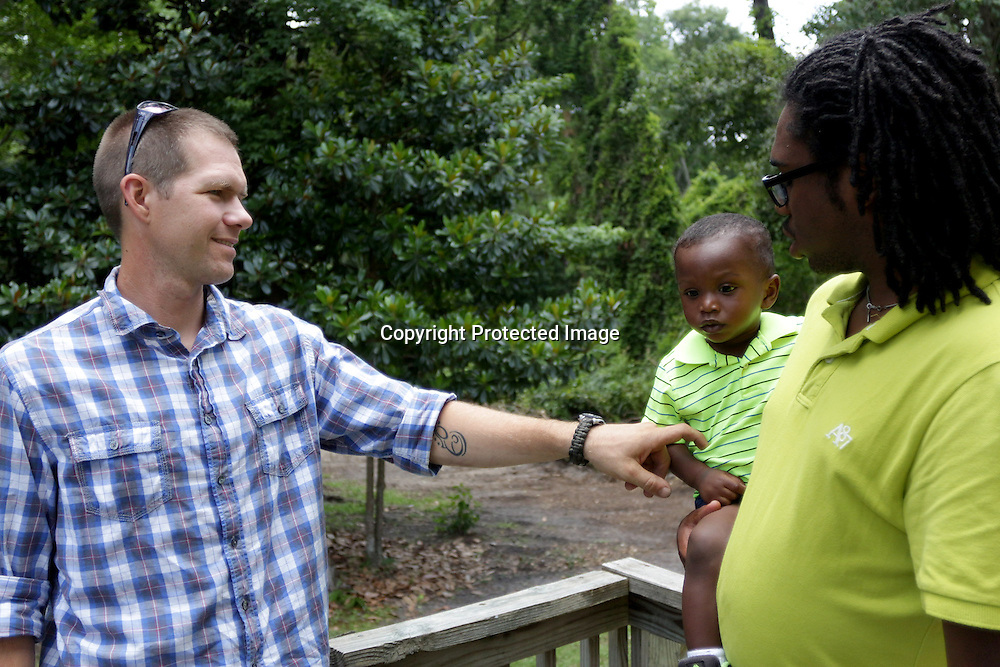 Site Supervisor, Josh Rammel, left, talks to Homeowner, Christian Pierce and Pierce's Godson Jasan Harper, 1, Sunday June 22, 2014 during a Cape Fear Habitat for Humanity dedication ceremony of a recently completed home on Tiffany Drive in Wilmington, N.C. (Jason A. Frizzelle)